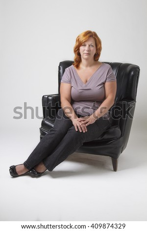 woman in her early forty with red hair sitting on a black leather love set - stock photo