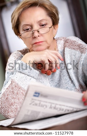 Woman in her fifties reading newspaper