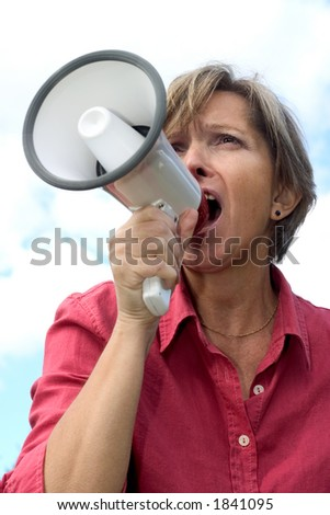 Woman in her fifties shouting through a megaphone. - stock photo