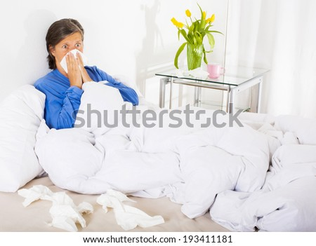 woman in her fifties sitting in her bed with a cold and blowing her nose - stock photo