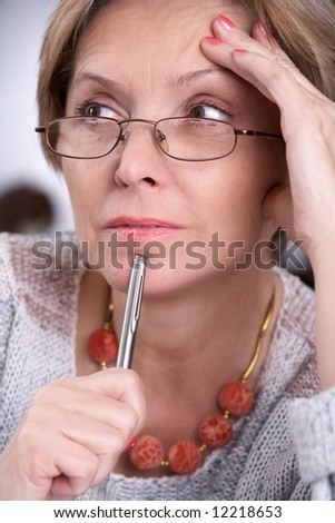 Woman in her fifties thinking, portrait. - stock photo