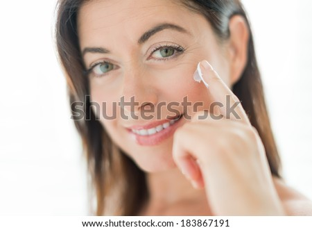 Woman in her forties applying  face cream - stock photo