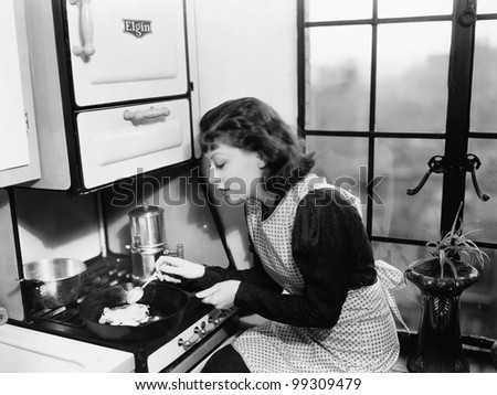 Woman in her kitchen preparing food on the stove