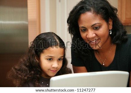 Woman in her kitchen with daughter on the computer - stock photo