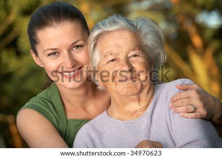 Woman in her late twenties embracing a senior lady