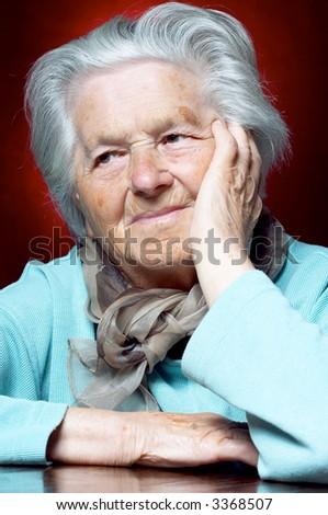 Woman in her nineties leaning on hand and looking away - stock photo