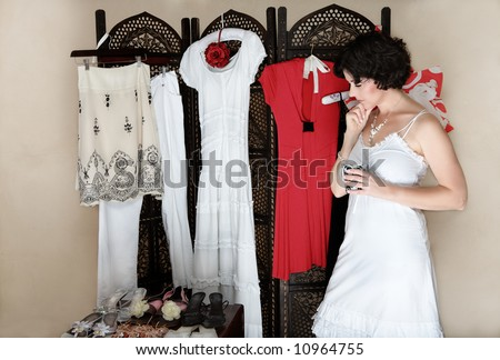 Woman in her 30s-40s standing next to a collection of shoes and other hanging clothes - thinking - stock photo