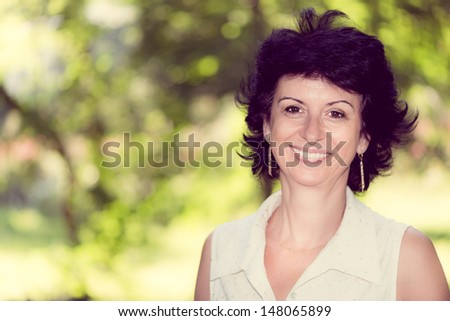 Woman in her 50s smiling outdoors portrait - stock photo