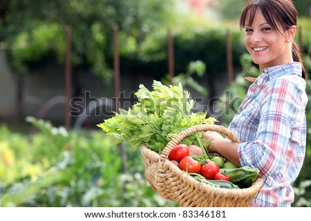 Woman in her vegetable garden - stock photo