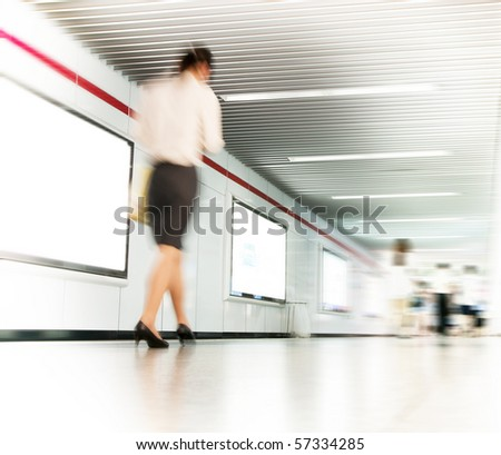 Woman in high heel shoes walking down a corridor, blurred motion - stock photo