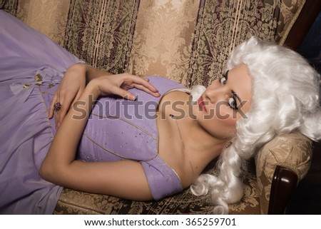 Woman in historic baroque style dress and white wig lying on the couch - stock photo