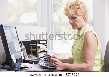 Woman in home office at computer with credit card frowning - stock photo