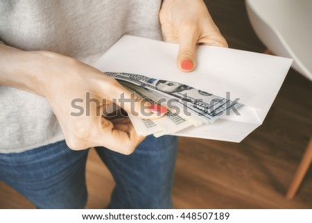 Woman in jeans and grey top holding envelope with cash. Concept of corruption and bribery