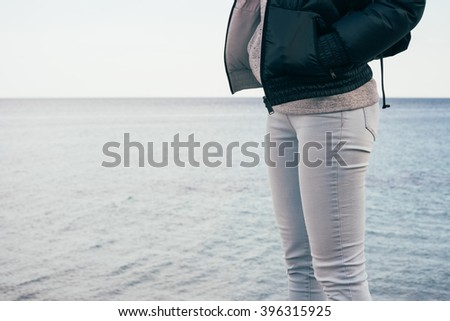 Woman in jeans and jacket standing on the sea background. Walking on the beach in the winter