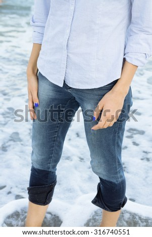 Woman in jeans and shirt standing in sea water barefoot. Details of women's clothing.