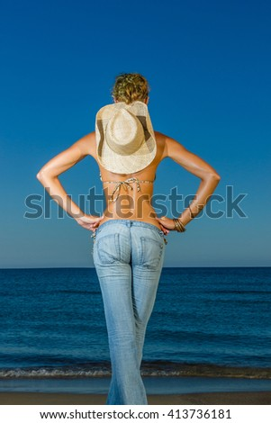 Woman in jeans and straw hat  at the beach in the summertime - stock photo