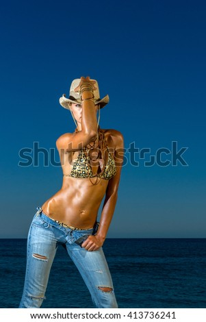 Woman in jeans and straw hat  at the beach in the summertime