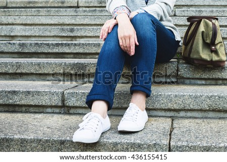 Woman in jeans with a bag sitting on the stairs