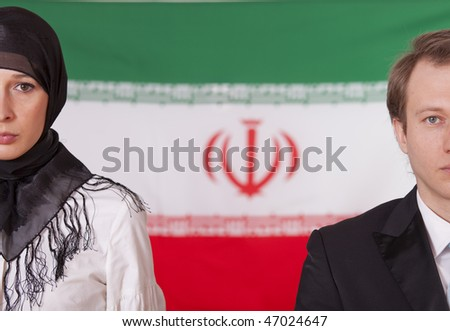 woman in kerchief and man posing in front of iran flag - stock photo