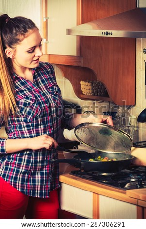 Woman in kitchen cooking stir fry frozen vegetables. Girl frying making delicious risotto. Dinner food meal. Instagram filtered. - stock photo