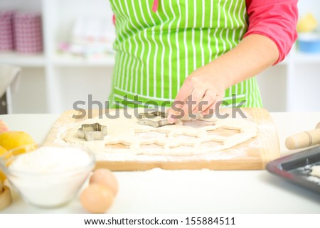 Woman in kitchen during cooking biscuits, close up