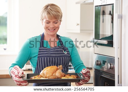 Woman In Kitchen Holding Tray With Roast Chicken - stock photo