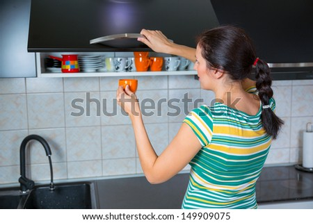 Woman in kitchen interior with clean dishes - stock photo