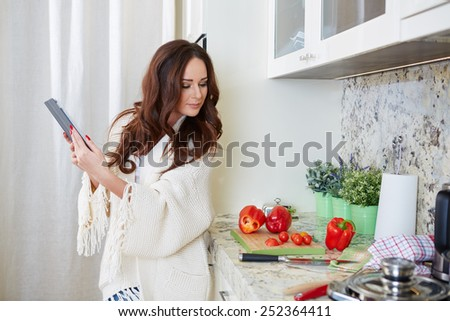 Woman in kitchen looking at recipe on tablet - stock photo