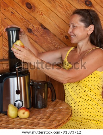Woman in kitchen making fresh squeezed juice using - stock photo