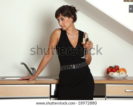 Woman in kitchen on a home party with champagne - stock photo