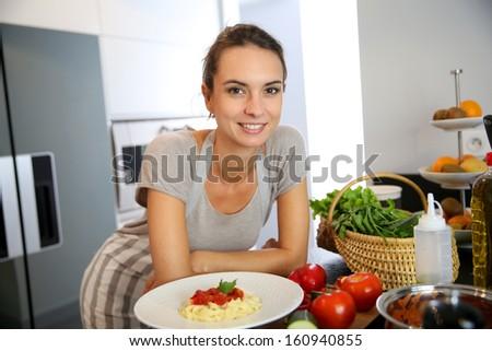 Woman in kitchen preparing pasta dish - stock photo