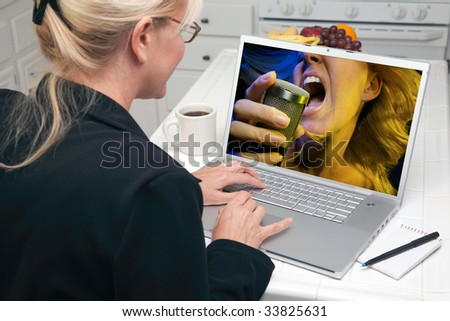 Woman In Kitchen Using Laptop for Music and Entertainment. Screen image can easily be replaced using the included clipping path. - stock photo