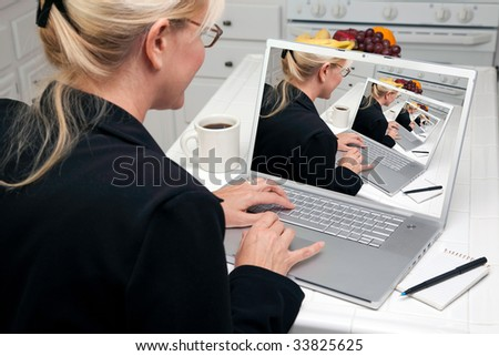 Woman In Kitchen Using Laptop. Screen image can easily be replaced using the included clipping path. - stock photo