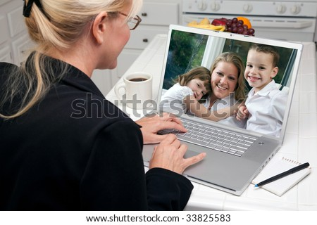 Woman In Kitchen Using Laptop See Friends and Family. Screen image can easily be replaced using the included clipping path. - stock photo