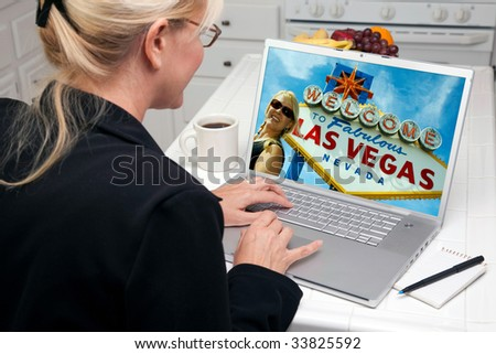 Woman In Kitchen Using Laptop to Research A Las Vegas Trip. Screen image can easily be replaced using the included clipping path. - stock photo