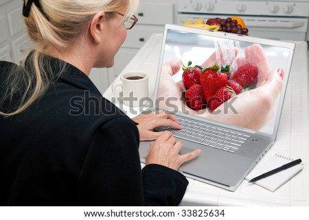 Woman In Kitchen Using Laptop to Research Cooking and Recipes. Screen image can easily be replaced using the included clipping path. - stock photo