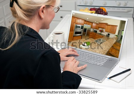 Woman In Kitchen Using Laptop to Research Home Improvement Ideas. Screen image can easily be replaced using the included clipping path. - stock photo