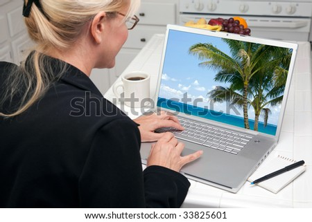 Woman In Kitchen Using Laptop to Research Travel and Vacations. Screen image can easily be replaced using the included clipping path. - stock photo