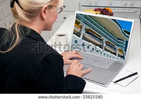 Woman In Kitchen Using Laptop to Research Travel, Vacation and Cruises. Screen image can easily be replaced using the included clipping path. - stock photo
