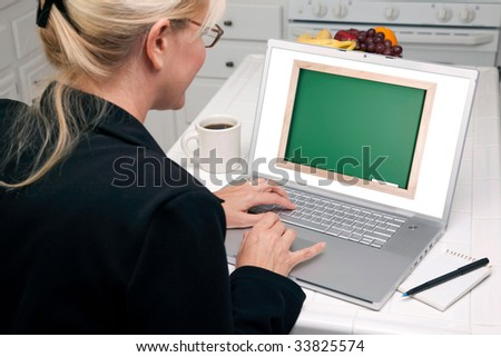 Woman In Kitchen Using Laptop with Blank Chalkboard ready for you own message. Screen image can easily be replaced using the included clipping path. - stock photo