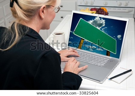 Woman In Kitchen Using Laptop with Blank Road Sign Ready for Your Own Message. Screen image can easily be replaced using the included clipping path. - stock photo