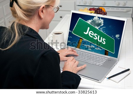 Woman In Kitchen Using Laptop with Jesus Road Sign on Screen. Screen image can easily be replaced using the included clipping path. - stock photo