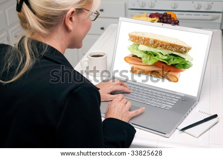 Woman In Kitchen Using Laptop with Large Sandwich on the Screen. Screen image can easily be replaced using the included clipping path. - stock photo