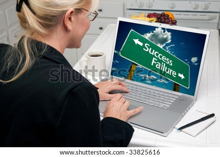 Woman In Kitchen Using Laptop with Success or Failure Road Sign on Screen. Screen image can easily be replaced using the included clipping path. - stock photo