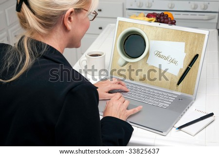 Woman In Kitchen Using Laptop with Thank You Image on Screen. Screen image can easily be replaced using the included clipping path. - stock photo