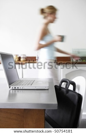 Woman in kitchen walking by laptop, focus on laptop - stock photo