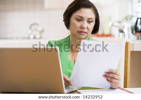 Woman in kitchen with laptop and paperwork looking worried - stock photo