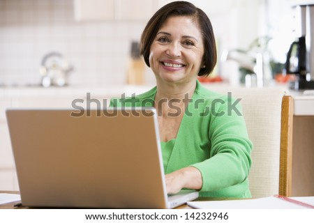 Woman in kitchen with laptop smiling - stock photo