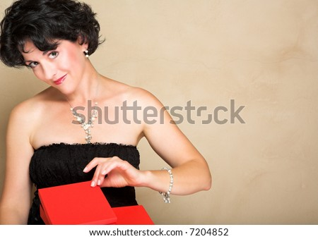 Woman in lace black dress with short curly hair, wearing pearls, opening a red gift box - stock photo