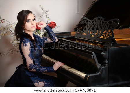 Woman in lace deep blue dress playing the piano. Retro vintage style - stock photo